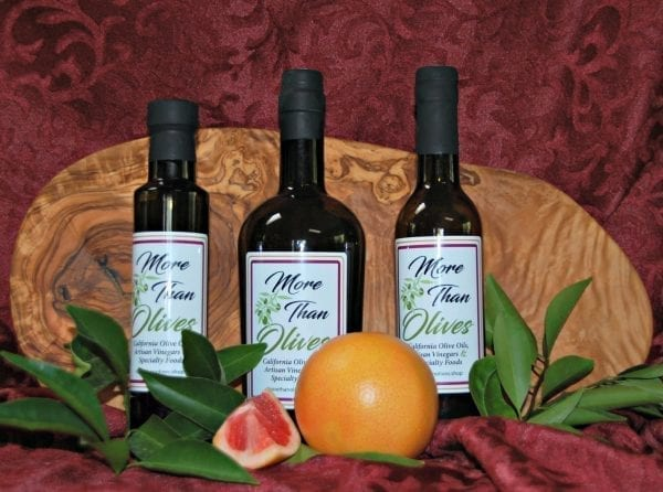 three bottles of olive oil and wood cutting board