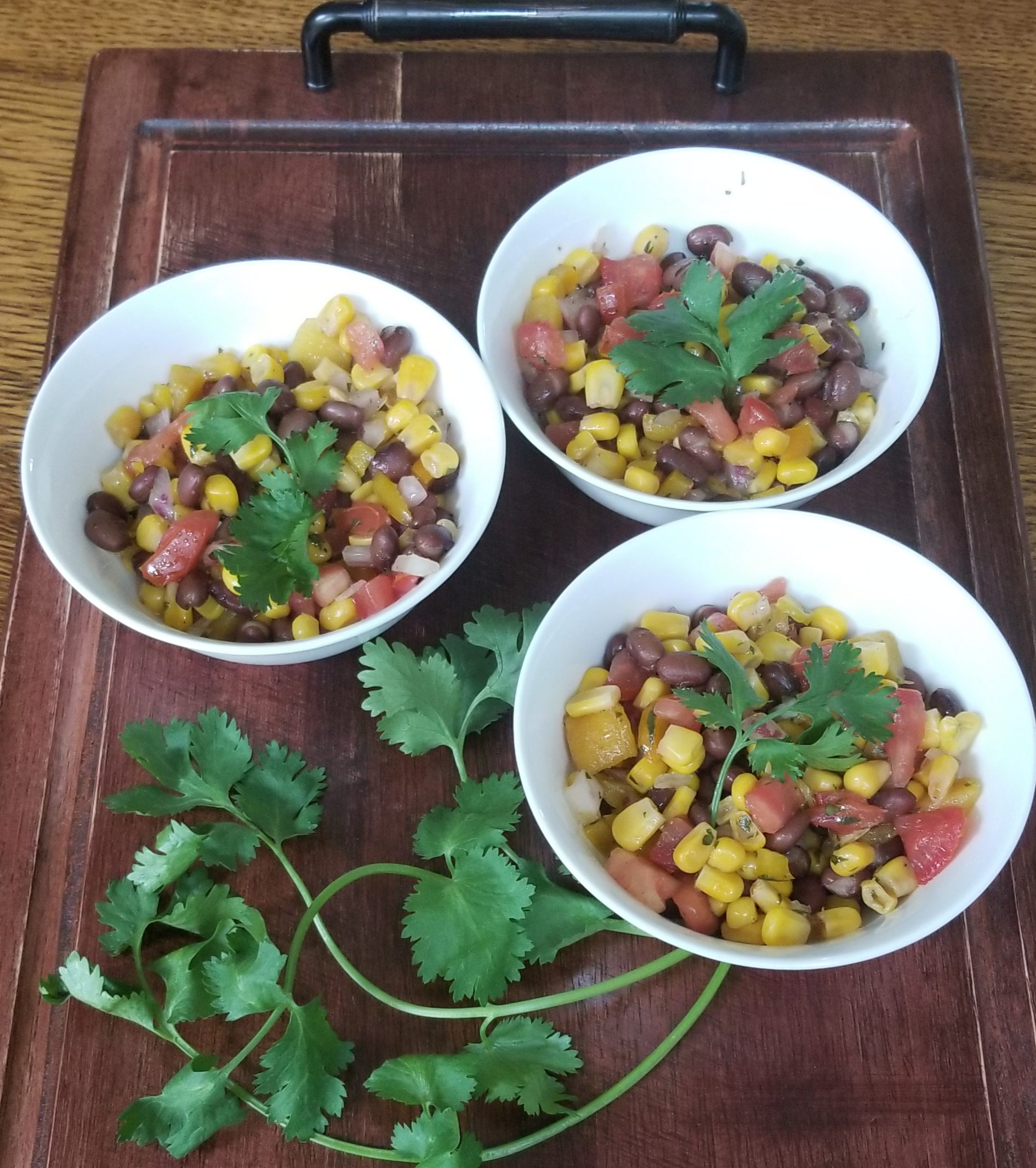Black bean and corn salad in three bowls on a serving tray